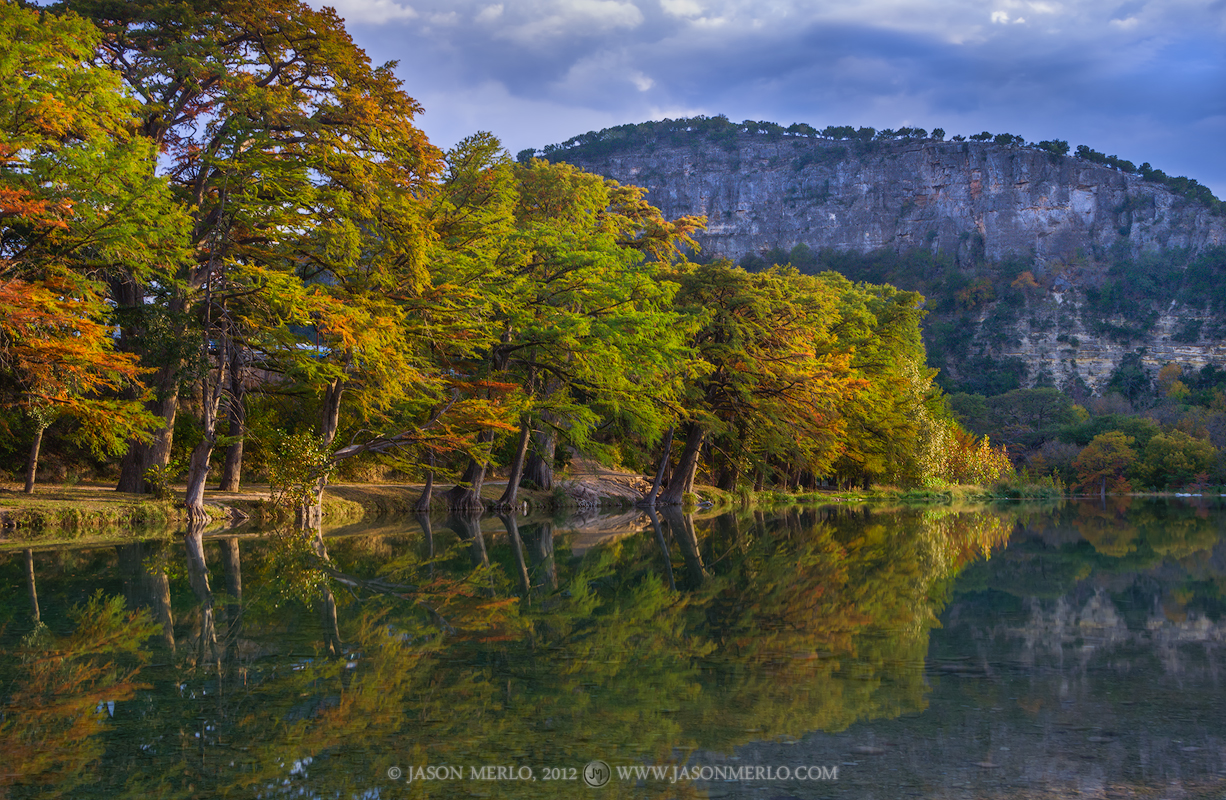 Cypress trees beneath Old Baldy are reflected in the Frio River near sunset at Garner State Park in Uvalde County in...