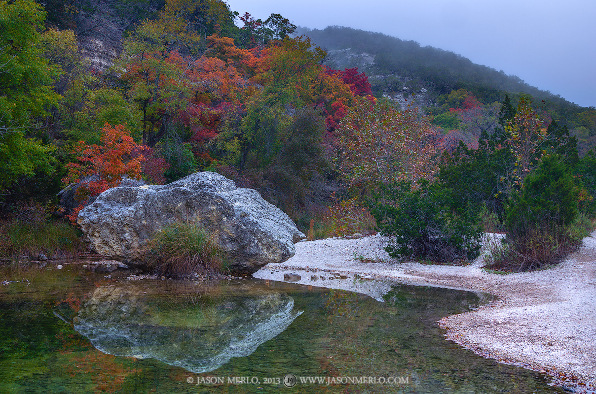 Bigtooth maple trees (Acer grandidentatum) in fall color and a boulder reflected in a pool on the Sabinal River under a layer...