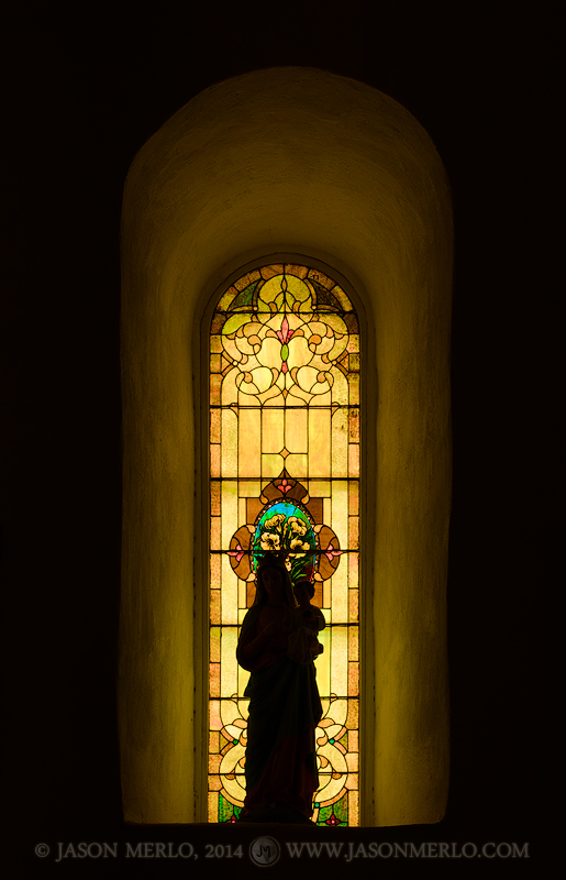Silhouette of a statue of the Virgin Mary in front of a stained glass window at San Elizario Presidio Chapel in San Elizario (...