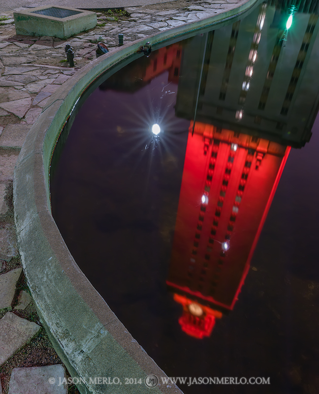 The Tower lit orange for the 2014 Distinguished Alumni Awards reflected in the Turtle Pond at the University of Texas in Austin...