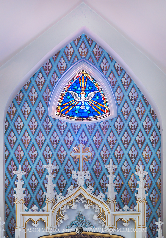 The painted apse and a stained glass window at Immaculate Conception of the Blessed Virgin Mary Catholic Church in Panna Maria...