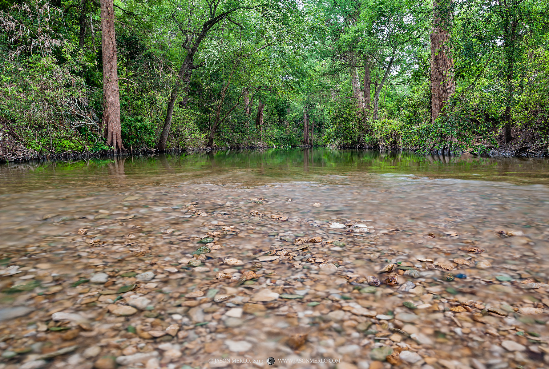 Shallow water runs over stones in a creek in the Texas Hill Country.