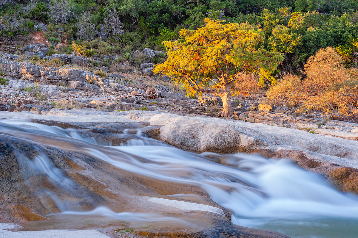 Shallow water runs over stones in Onion Creek at Camp Ben McCulloch in Hays County, Texas.
